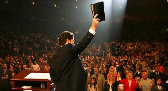 Popular Christian Pastor Joel Osteen holds up his Bible before a service.